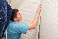 Trabajador joven que alisa el papel pintado Imagen de archivo
