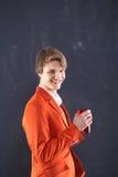 Trabajador joven sonriente con la taza roja Imagen de archivo libre de regalías
