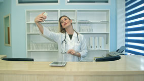 Trabajador médico de sexo femenino sonriente que toma selfies con su teléfono en el mostrador de recepción Foto de archivo libre de regalías