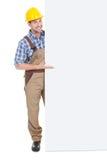 Trabajador manual confiado que sostiene la cartelera Imagen de archivo
