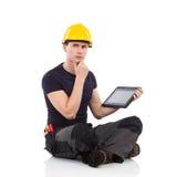 Trabajador manual de pensamiento que presenta con una tableta digital Imagenes de archivo