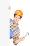 Trabajador manual joven con el casco que sostiene una llave Imagen de archivo libre de regalías