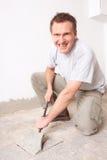 Trabajador manual que desensambla los azulejos de suelo viejos Foto de archivo