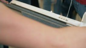 Trabajador manual que hace textura hecha punto en el telar en la fábrica de la materia textil Ciérrese encima del hilo para obras metrajes