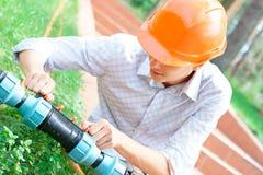 Trabajador manual que repara un tubo Imagen de archivo libre de regalías