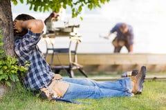 Trabajador manual que se inclina en tronco de árbol Fotos de archivo libres de regalías