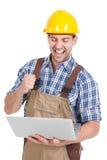 Trabajador manual que usa el ordenador portátil Fotos de archivo libres de regalías