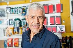 Trabajador mayor confiado que sonríe en tienda del hardware Foto de archivo libre de regalías