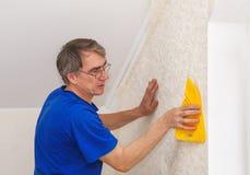 Trabajador mayor que alisa el papel pintado Imagenes de archivo