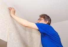 Trabajador mayor que ata el papel pintado Foto de archivo libre de regalías