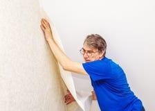 Trabajador mayor que ata el papel pintado Fotos de archivo libres de regalías