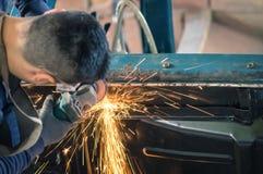 Trabajador mecánico del hombre joven que repara una vieja carrocería del vintage fotos de archivo libres de regalías
