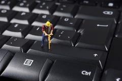 Trabajador miniatura encima del teclado de ordenador negro imagenes de archivo