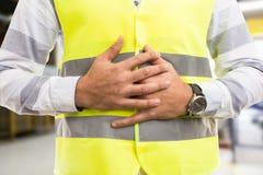Trabajador o ingeniero de construcción que presiona el estómago doloroso foto de archivo