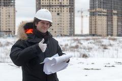Trabajador o ingeniero que sostiene el dibujo en manos y la lectura él en fondo de las nuevas construcciones y construcción de vi Imagen de archivo