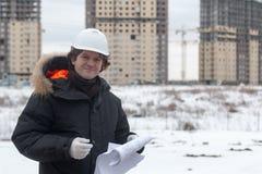 Trabajador o ingeniero que sostiene el dibujo en manos y la lectura él en fondo de las nuevas construcciones y construcción de vi Foto de archivo