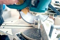 Trabajador o manitas que corta perfil del PVC con la sierra circular Foto de archivo libre de regalías