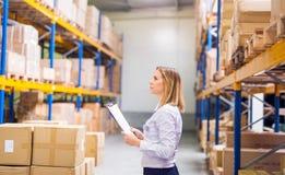 Trabajador o supervisor del almacén de la mujer con el tablero Imágenes de archivo libres de regalías