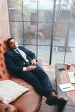 Trabajador perezoso que miente en el sofá en oficina foto de archivo