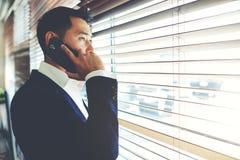 Trabajador profesional confiado que tiene conversación telefónica móvil con su socio comercial imágenes de archivo libres de regalías