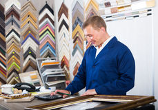 Trabajador profesional que lleva a cabo moldear que enmarca de la imagen de madera Foto de archivo