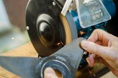Trabajador que afila su cortacésped de la cuchilla Fotos de archivo libres de regalías