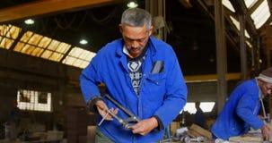 Trabajador que ajusta la abrazadera en el taller 4k de la fundición almacen de metraje de vídeo