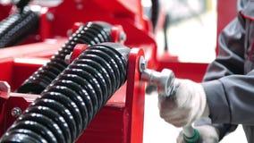 Trabajador que aprieta la nuez en el amortiguador de choque de la unidad agrícola con la llave de zócalo almacen de metraje de vídeo