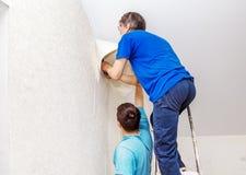 Trabajador que ata el papel pintado Foto de archivo