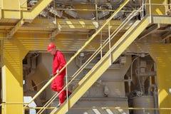 Trabajador que camina abajo de las escaleras en planta imagen de archivo