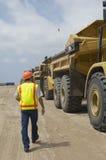 Trabajador que camina cerca de los camiones en el vertedero imagen de archivo