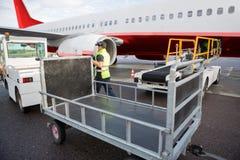 Trabajador que camina entre el camión y el aeroplano en pista Foto de archivo