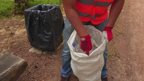 Trabajador que clasifica las botellas plásticas en bolso metrajes