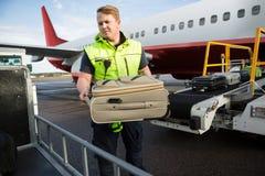 Trabajador que coloca el equipaje en remolque contra el aeroplano Foto de archivo