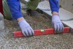 Trabajador que comprueba el nivel horizontal de tierra para saber si hay pavimentar imagen de archivo