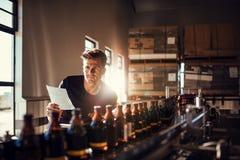 Trabajador que comprueba el proceso en la cadena de producción en la cervecería fa fotografía de archivo