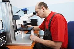 Trabajador que comprueba la punta de prueba con el microscopio industrial imagenes de archivo