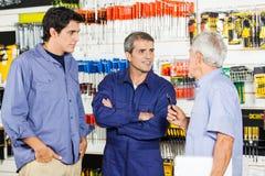Trabajador que comunica con los clientes en hardware Foto de archivo