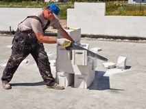 Trabajador que corta los bloques de cemento Fotos de archivo libres de regalías