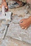Trabajador que corta un azulejo. Imagen de archivo libre de regalías
