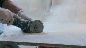 Trabajador que corta una teja usando una amoladora de ángulo en el emplazamiento de la obra almacen de video