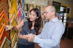 Trabajador que elige el marco en moldear que enmarca en taller Imagenes de archivo