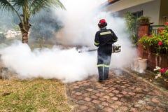 Trabajador que empaña área residencial con los insecticidas para matar al aedes Fotos de archivo libres de regalías