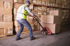 Trabajador que empuja la carretilla con las cajas en almacén Fotos de archivo