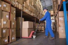 Trabajador que empuja la carretilla con las cajas en almacén Imagenes de archivo