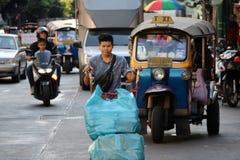 Trabajador que empuja la carretilla de dos ruedas en el camino a la mercancía de la entrega en la ciudad comercial de Sampheng, B fotografía de archivo