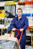Trabajador que empuja la carretilla en tienda del hardware Fotos de archivo libres de regalías