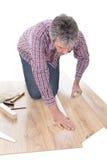 Trabajador que ensambla el suelo laminado imágenes de archivo libres de regalías