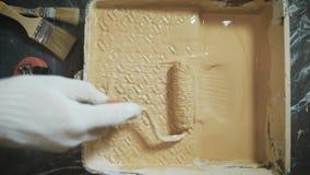 Trabajador que escoge un rodillo de pintura en una bandeja especial almacen de video