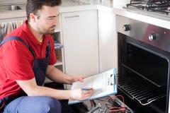 Trabajador que estima el coste para el horno quebrado imagenes de archivo